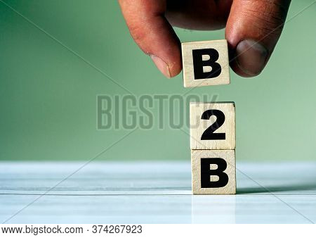 The Hand Puts The Cube Block With The Inscription B2b. Business To Business Concept Background.