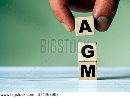 The Hand Puts The Cube Block With The Inscription Agm. Annual General Meeting - Acronym On Wooden Cu