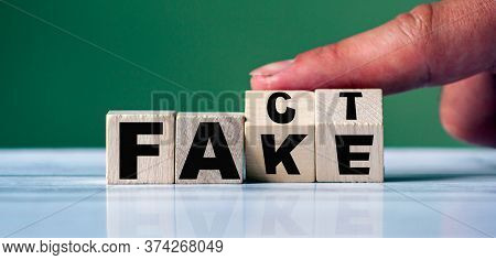 Hand Turn Word Fake To Fact On Wooden Cube Blocks.