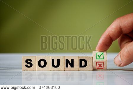 The Hand Turns The Wooden Cube And Changes The Word Sound With Green Positive Tick Check Box And Red