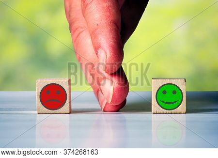 The Hand Separates Two Wooden Blocki With Red Sad Face And Green Happy Face. Symbol For The Differen