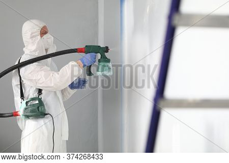 Close-up Of Professional Male Worker Painting Wall In Grey Colour With Spray Gun. Adult Man In White