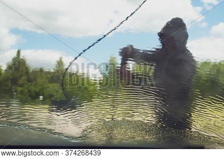 Man Washing His Car, Close-up. Close-up Of Man Holding A High-pressure Water Sprayer For Door Car Wa