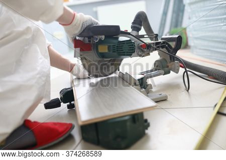 Close-up Of Professional Foreman Working With Metal Electrical Instrument. Man In Protective White G