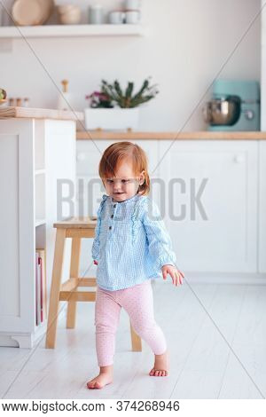 Cute Happy Infant Baby Girl Walking On The Kitchen At Home