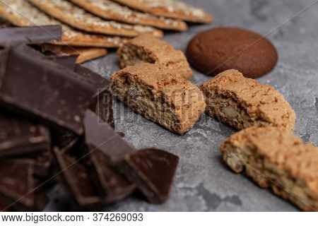 Cookies And Dark Chocolate On Concrete Textured Background.