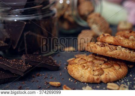 Dark Chocolate And Peanut Cookies On Dark Blurred Background.