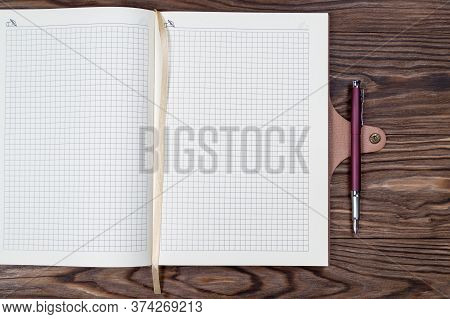 Open Daily Planner On Wooden Background With Fountain Pen. Copyspace Template And Branding Mockup.