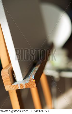A Part Of Art Easel With Brush On Soft Blurred Backgrounnd