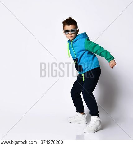 Little Kid In Sunglasses, Colorful Tracksuit And Sneakers. He Is Posing In A Jump, Isolated On A Whi