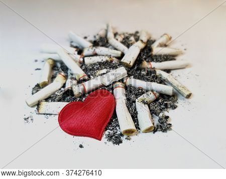 Closeup Red Heart Lies On A Pile Of Cigarette Butts And Ashes On A White Background. Symbol Of The H
