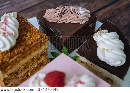 Collection Of Various Cakes On Wood Background. Assortment Of Pieces Slices With Cream. Plate With D