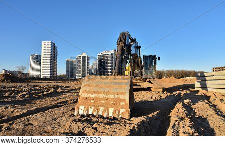 Excavators At Earthworks On Construction Site. Backhoe Loader Digs A Pit For The Construction Of The