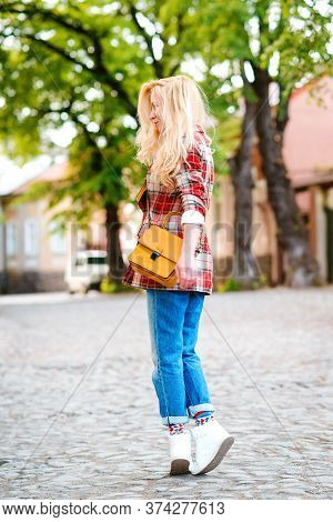 Young Stylish Hipster Woman Walking On The Street. Girl Wearing Trendy Outfit. Woman Enjoy Her Weeke