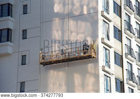 Builder On Suspended Construction Cradle Paint The Shasad Of A New Residential Building. Mobile Scaf