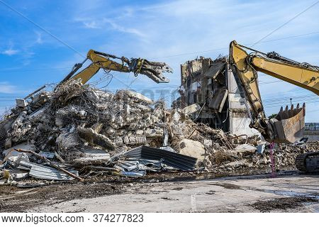 Building House Demolition Site Excavator With Hydraulic Crasher Machine And Yellow Container