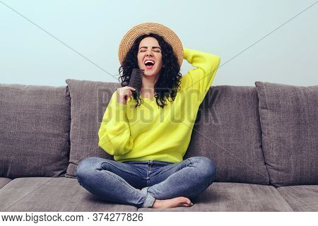 Brunette Woman Combing Her Curly Hair At Home. Pretty Woman Wears Hat And Yellow Pullover. Beauty An