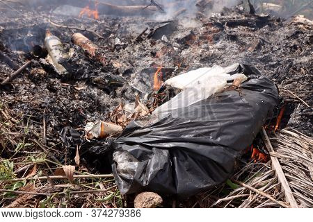 Plastic household garbage burning and releasing carbon dioxide and toxic chemicals which pollute the air
