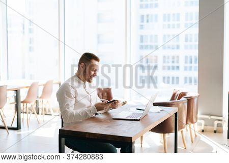 Cheerful Young Business Man Wearing In Casual Clothes Is Working On Laptop Computer At The Desk In O