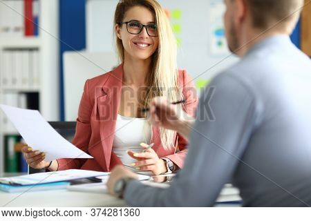 Portrait Of Smiling Charming Female Discussing Contract With Partner. Attractive Young Woman In Clas