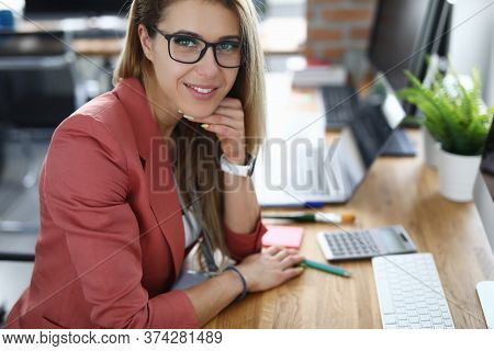 Portrait Of Lovely Female Accountant Sitting On Working Place. Well-dressed Young Woman Wearing Blac