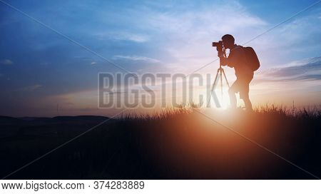 Silhouette Of Photographer Taking Picture Using Dslr Camera And Tripod On Sunset Or Sunrise Backgrou