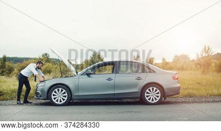 Businessman Examining Broken Down Car Looking At Engine Under Open Motor Hood In Countryside, Side V
