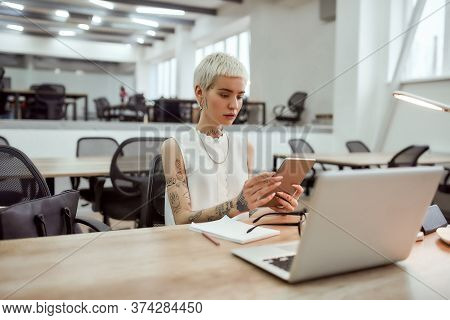 Young Stylish Blonde Tattooed Business Woman Using Touchpad, Sitting At Her Working Place In The Mod