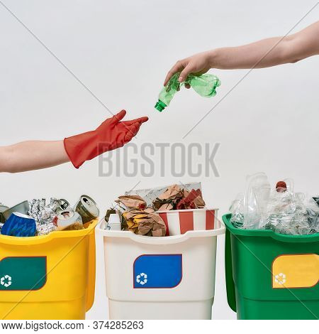 Hand Giving Plastic Bottle To Another Hand In Red Glove Over Three Colorful Green, Yellow And White