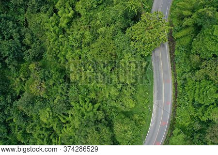 Road winding through forest from aerial drone. Scenic route in Thailand