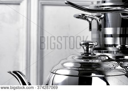 Aluminum Cookware On Black Induction Stove Against Grey Wall