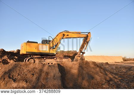 Excavator Working On Earthmoving. Backhoe Digs Ground In Sand Quarry On Blue Sky Background. Constru