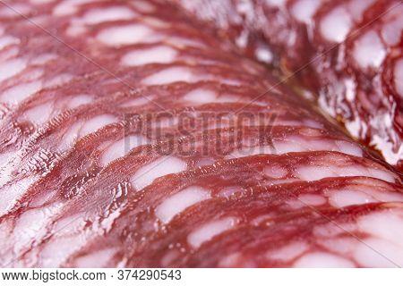 Top View Macro Shot Of Smoked Pork Salami Chorizo Sausages Slices Background. Raw Smoked Salami Saus