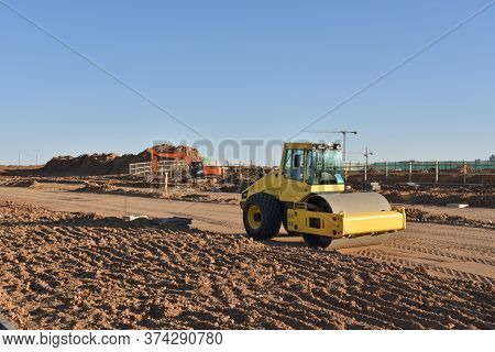 Soil Compactor The Leveling Soil At Construction Site. Excavator And Vibration Single-cylinder Road