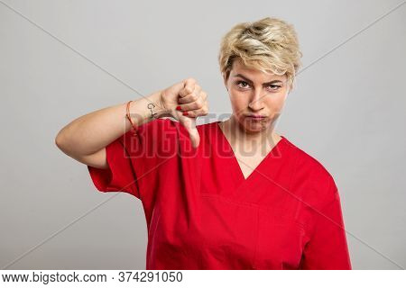 Portrait Of Young Attractive Female Nurse Showing Dislike Gesture
