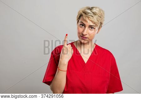 Portrait Of Young Attractive Female Nurse Showing Number One