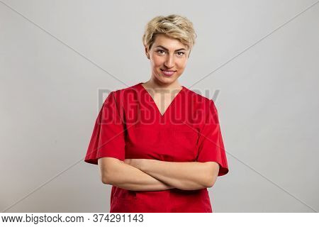 Portrait Of Young Attractive Female Nurse Standing With Arms Crossed