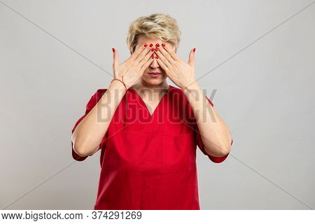 Portrait Of Young Attractive Female Nurse Covering Eyes