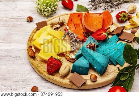 Cheese Plate. Assorted Multicolored Hard Dutch Cheeses. Blue And Red Pesto, Aged Gouda