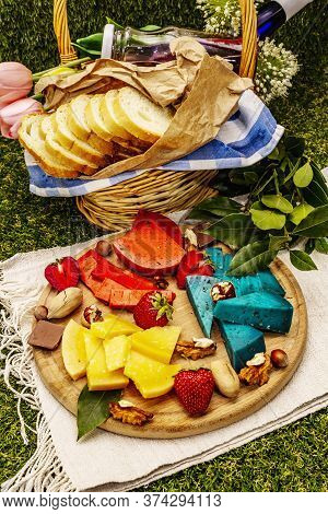 Picnic Concept. Assorted Multicolored Hard Dutch Cheeses. Blue And Red Pesto, Aged Gouda. Strawberry