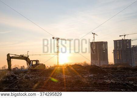 Excavator During Earthmoving At Construction Site On Sunset Background. Onstruction Machinery For Ex