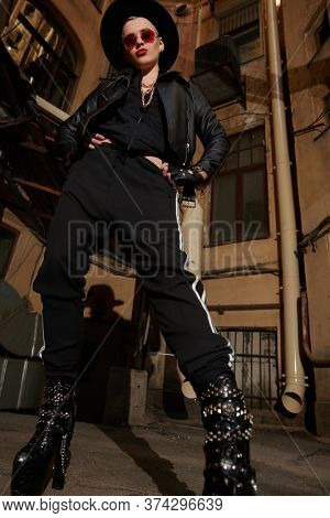 A portrait of a stylish punk woman in the street. Modern punk fashion.