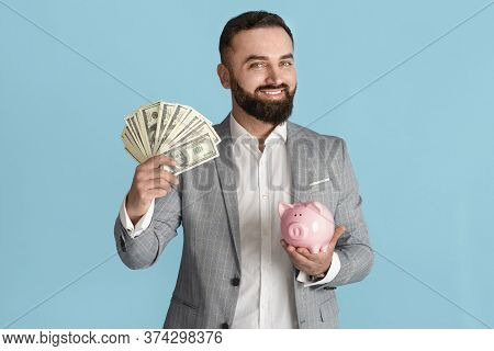 Smiling Entrepreneur With Lots Of Money And Piggybank Against Blue Background