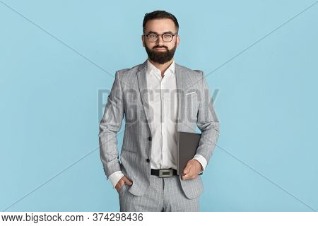 Confident Business Owner In Formalwear And Glasses Holding Tablet Computer Against Blue Background