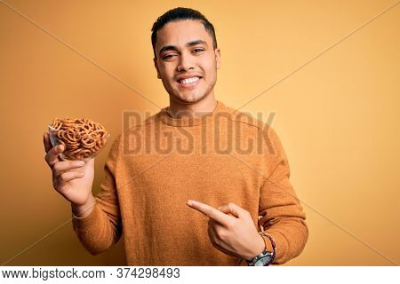 Young brazilian man holding bowl with german salty baked pretzels over yellow background very happy pointing with hand and finger