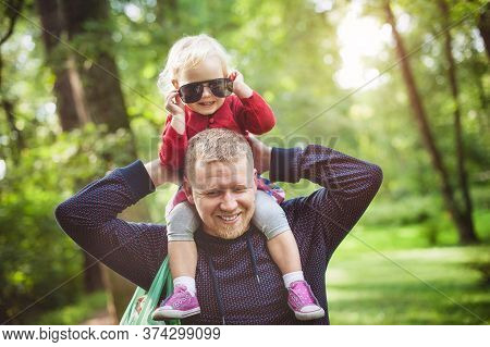 The Man Put A Little Blonde Girl On The Neck, They Are Smiling. Dad Holds His Daughter On His Should