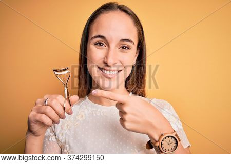 Young beautiful woman using eyelash curler standing over isolated yellow background very happy pointing with hand and finger
