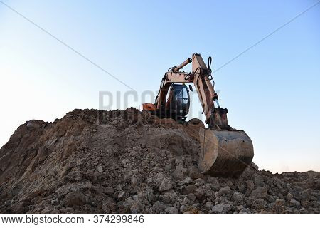 Bucked Wheel Excavator On Earthmoving. Backhoe Digs Ground In Sand Quarry On Blue Sky Background. Co