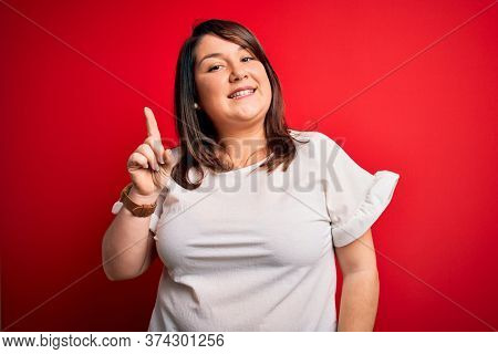 Beautiful brunette plus size woman wearing casual t-shirt over isolated red background showing and pointing up with finger number one while smiling confident and happy.