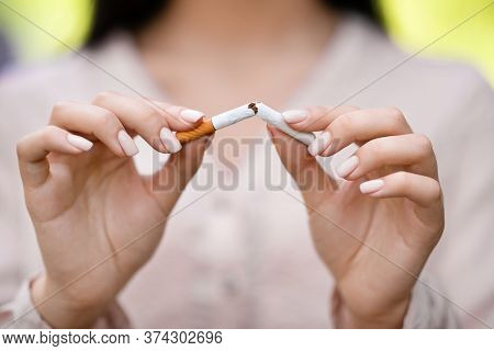 Stop Smoking Concept. Unrecognizable Woman Breaking Cigarette Outdoors, Closeup Image With Selective